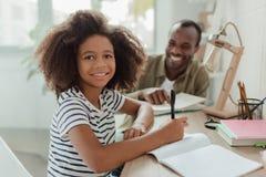 做与爸爸的小女孩家庭作业 免版税图库摄影