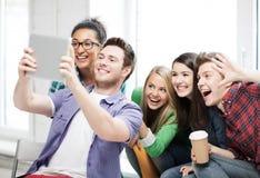 做与片剂个人计算机的学生图片在学校 图库摄影