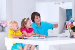 做与现代计算机的孩子家庭作业 免版税库存图片