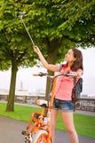 做与电自行车的行家女孩selfie反对绿色城市 免版税库存图片