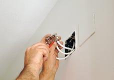 做与电视天线的一位合格的电工接线连接在房子的整修的接线盒 免版税图库摄影