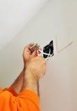 做与电视天线的一位合格的电工接线连接在房子的整修的接线盒 免版税库存图片