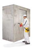 做与穿孔器的工作者一个孔在水泥墙壁 库存照片