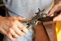 做与穿孔机的孔在皮革车间 有e的男性手 库存图片
