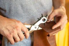 做与穿孔机的孔在皮革车间 有e的男性手 免版税库存图片