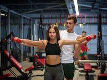 做与红色哑铃的夫人锻炼在健身房背景 帮助健身俱乐部的一位个人教练员一个客户 库存照片