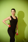 做与红色哑铃的美丽的女孩锻炼 库存照片