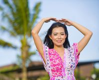 做与胳膊的年轻愉快的美丽的亚裔中国旅游妇女爱标志在她的摆在和嘲笑海滩热带r的头上 库存图片