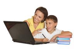 做与膝上型计算机的母亲和儿子家庭作业 库存照片