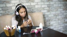 做与自由和拷贝空间的耳机听的音乐的逗人喜爱的女孩修指甲擦亮的钉子 免版税库存图片
