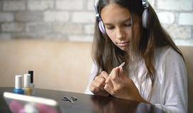 做与自由和拷贝空间的耳机听的音乐的逗人喜爱的女孩修指甲擦亮的钉子 库存图片