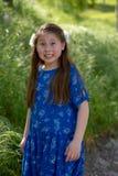 做与舌头的蓝色礼服的女孩滑稽和疯狂的面孔在绿色领域前面 免版税库存照片