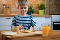 做与花生酱的男孩一个三明治在厨房 免版税库存照片