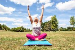 做与被舒展的胳膊的思考的少妇瑜伽 免版税库存图片