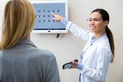做与视力检查表的美丽的眼镜师眼睛测试在她的眼科学诊所的患者 免版税图库摄影