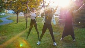 做与辅导员的两年轻女人瑜伽锻炼在公园在阳光下-一名妇女有长的蓝色dreadlocks 股票视频