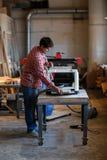 做与边缘飞机的老人木匠业在工作凳 免版税库存图片