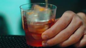 做与酒精饮料的侍酒者鸡尾酒与在玻璃的冰在酒吧 股票录像