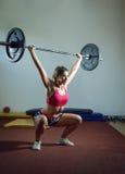 做与重量的女孩蹲坐 库存图片