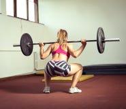做与重量的女孩蹲坐 免版税图库摄影