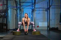 做与重量的灰色运动服的美丽的少妇锻炼 十字架适合 免版税图库摄影