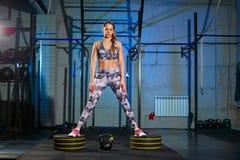 做与重量的灰色运动服的美丽的少妇锻炼 十字架适合 库存图片