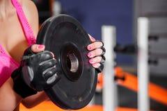 做与重量级的杠铃板材的女性手特写镜头锻炼在健身房 Crossfit锻炼 免版税库存照片