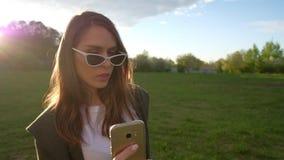 做与金黄智能手机的美丽的年轻女人selfie在公园 股票录像