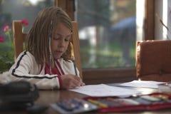 做与铅笔和纸的女孩家庭作业 免版税库存照片