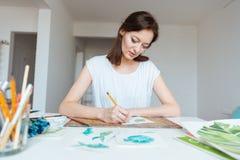 做与铅笔的被集中的妇女画家剪影在艺术演播室 库存照片