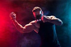 做与链子的严肃的肌肉战斗机拳打编辫子在他的拳头 库存照片