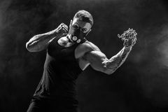 做与链子的严肃的肌肉战斗机拳打编辫子在他的拳头 免版税库存图片