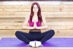 做与闭合的眼睛的妇女瑜伽 免版税库存图片