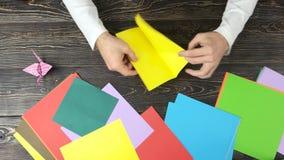 做与黄色纸的男性手origami 股票视频
