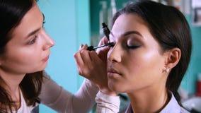 做与黑眼线膏的专业脸艺术家构成美丽的妇女的 股票录像