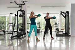 做与水壶响铃的健康年轻夫妇锻炼 库存照片