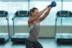 做与水壶响铃的健身妇女锻炼 库存照片