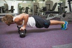 做与水壶响铃的年轻人俯卧撑在健身房 库存照片