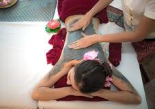 做与治疗泥的男按摩师按摩温泉在泰国温泉生活方式的亚裔妇女身体,因此放松和豪华 免版税库存图片