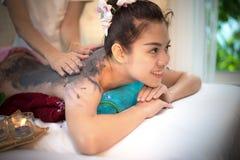 做与治疗泥的男按摩师按摩温泉在泰国温泉生活方式的亚裔妇女身体,因此放松和豪华 库存照片