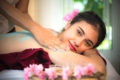 做与治疗的男按摩师按摩在泰国温泉生活方式的亚裔妇女身体,因此放松和豪华 免版税库存照片