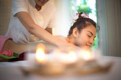 做与治疗的男按摩师按摩温泉在泰国温泉生活方式的亚裔妇女身体,因此放松和豪华 免版税库存照片