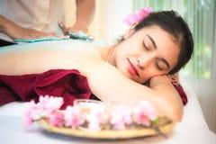 做与治疗的男按摩师按摩温泉在泰国温泉生活方式的亚裔妇女身体,因此放松和豪华 免版税图库摄影