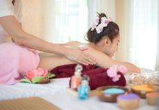 做与治疗的男按摩师按摩温泉在泰国温泉生活方式的亚裔妇女身体,因此放松和豪华 免版税库存图片
