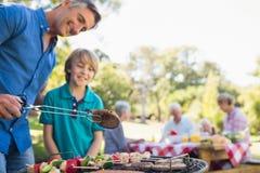 做与他的儿子的愉快的父亲烤肉 免版税库存图片