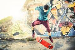 做与他的冰鞋的运动的溜冰者一个把戏在日落 免版税图库摄影