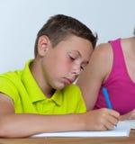 做与他的母亲的沉思非离子活性剂男孩家庭作业 免版税库存图片
