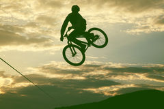 做与bmx自行车的一个人的剪影一个跃迁 免版税图库摄影
