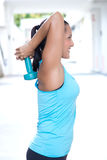 做与dumbbel的妇女双重引伸上升了在和在她的头后上 图库摄影