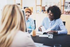 做业务会议的美丽的妇女的配合概念在现代办公室 一起谈论三个女孩的工友新的fashi 免版税库存图片
